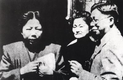 """中共代表邓颖超在上海举行的""""李闻两先生追悼会""""上宣读周恩来所写的悼词。中为民盟中央常委史良。"""