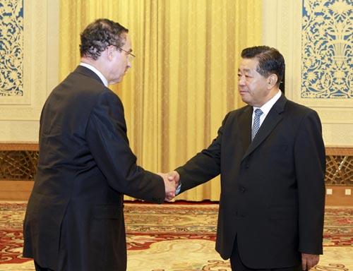 """6月27日,全国政协主席贾庆林在北京人民大会堂会见出席""""2012城市可持续发展北京论坛""""的美国华盛顿特区市长文森特·格雷等外国城市市长和副市长。这是贾庆林与文森特·格雷握手。新华社记者丁林摄"""